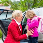 Mother consoling daughter on first day at school